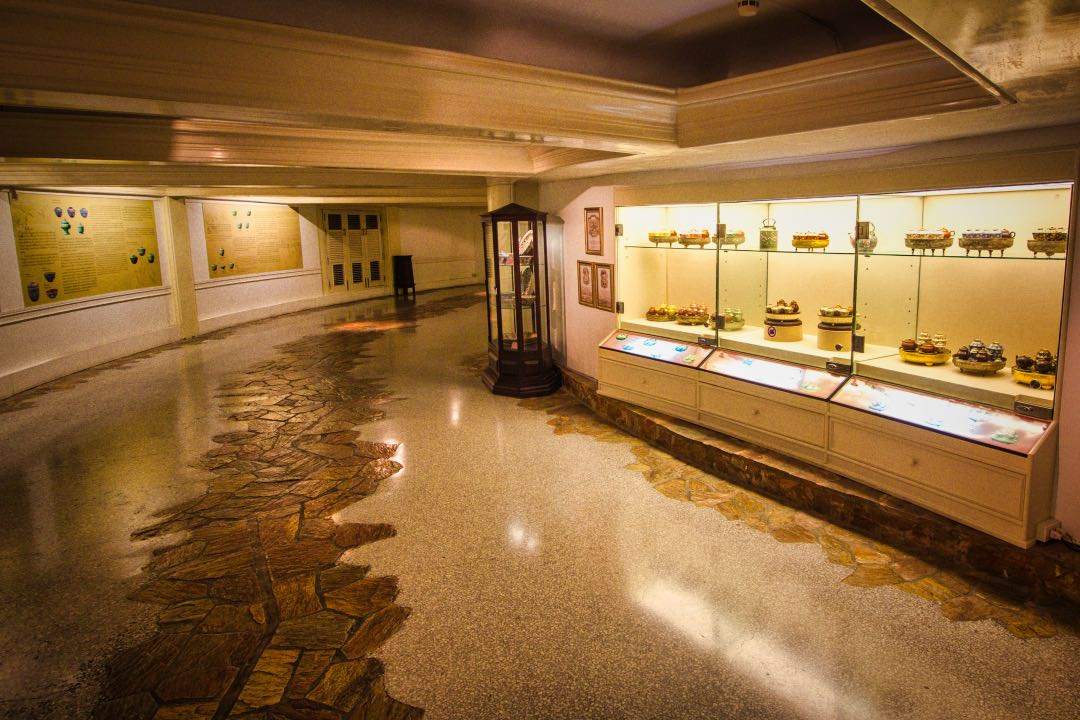 Low-ceiling basement room with lighted display cases filled with ornate pottery.