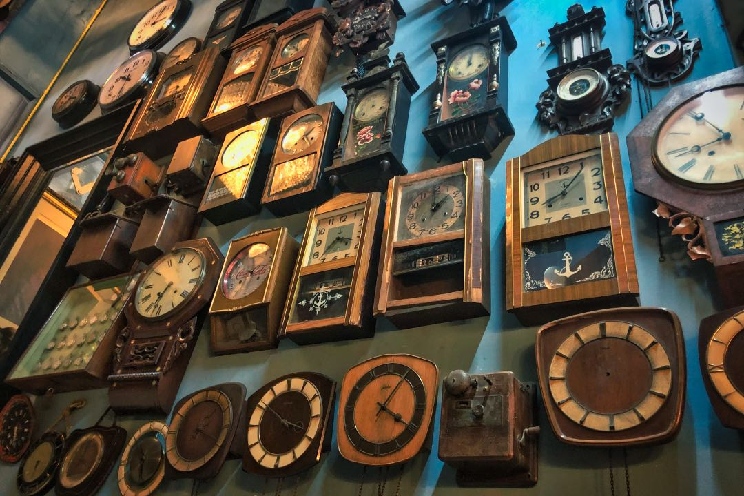 Varying styles of vintage clocks on a blue wall.