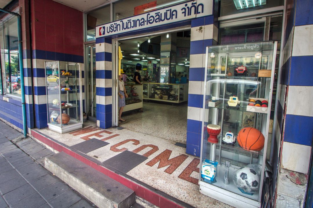 Department store entrance flanked by two glasses cases containing knick knacks like a soccer ball, billiard balls, and small toys.