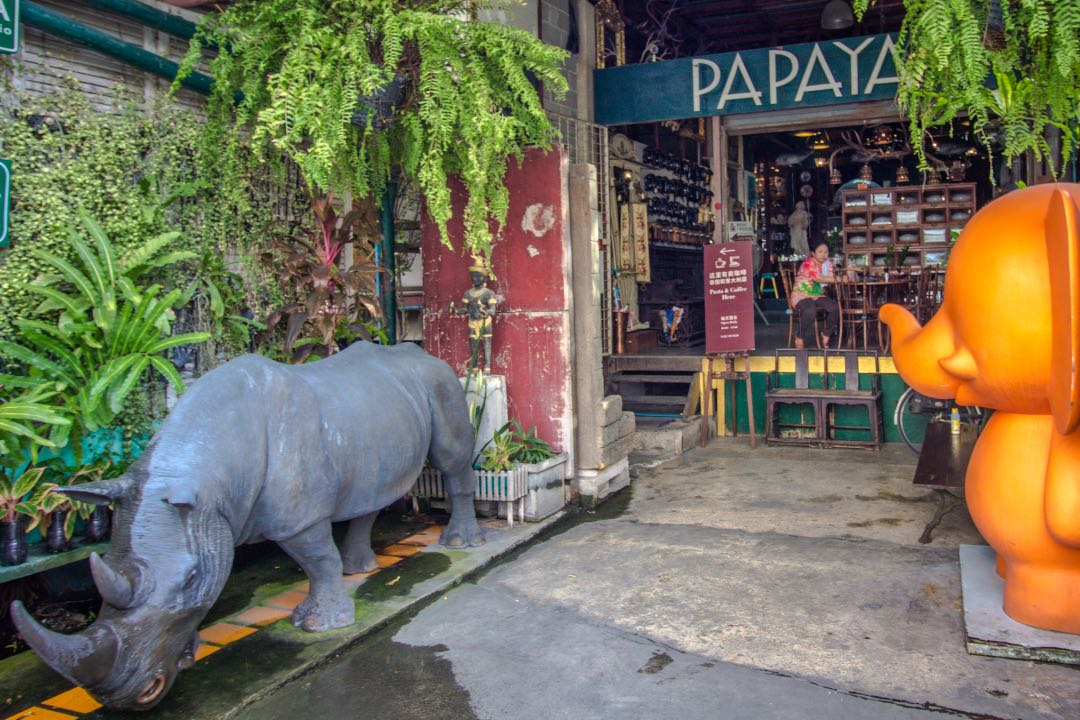Rhino and elephant statues outside shabby chic storefront.