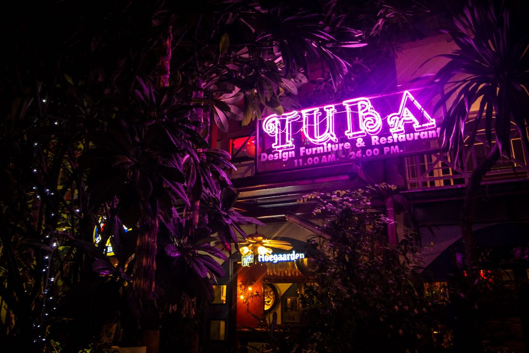 Lit up purple neon sign that says Tuba Design, Furniture, and Restaurant amongst palm leaves.