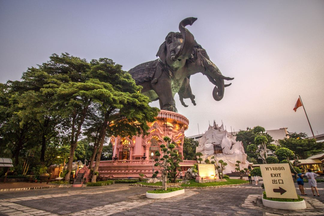 Massive elephant statue on an ornate pedestal looms over courtyard filled with tourists.