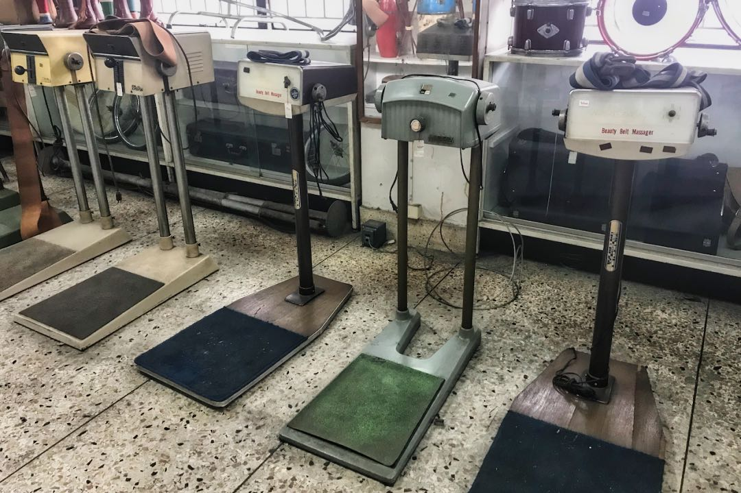 Row of antique belt massager exercise machines in front of glass display cases.