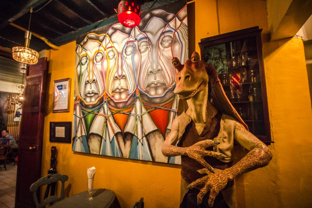 Jar Jar Binks statue in front of yellow wall with avant garde portrait in the background.