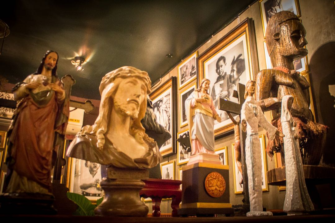 Ceramic Jesus Christ busts with framed photos of Thai families in the background.