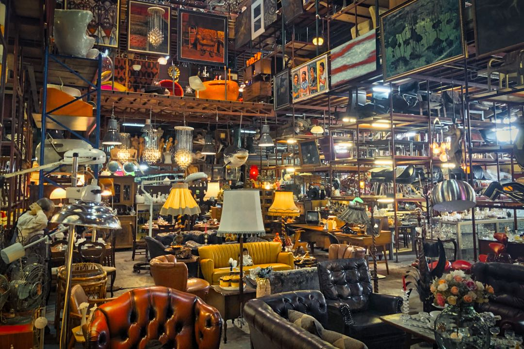 Cavernous warehouse space filled with vintage couches, chairs, and lamps.