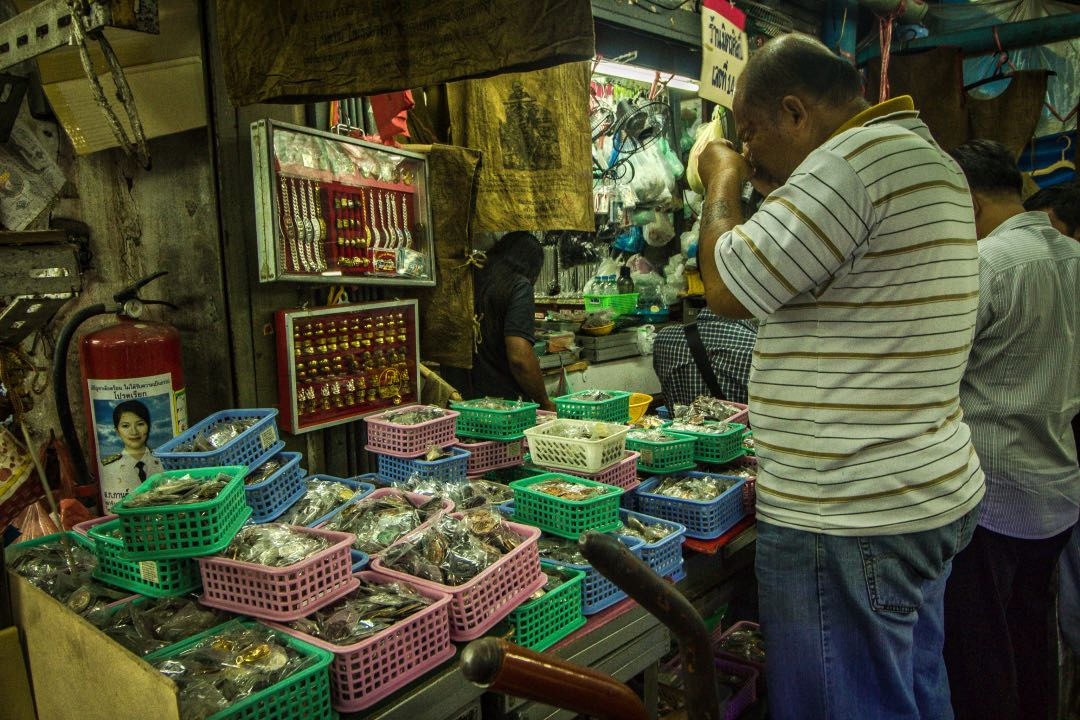 Middle-aged man carefully examining small amulets in a crowded market filled with plastic bins containing amulets.