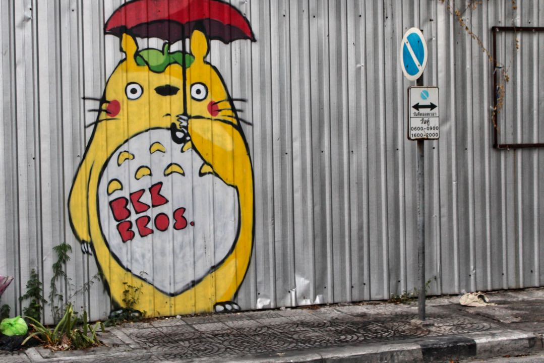 Corrugated metal fence with yellow cat mural painted on it.