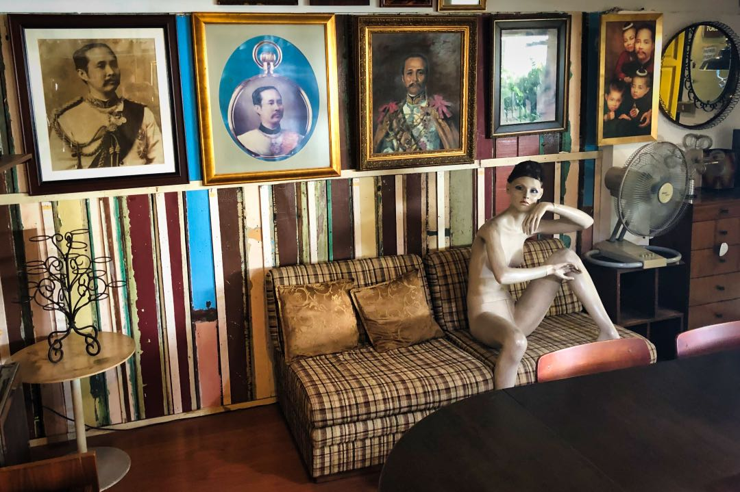 Naked mannequin seated on a vintage-patterned couch with old portraits hanging on the wall behind it.
