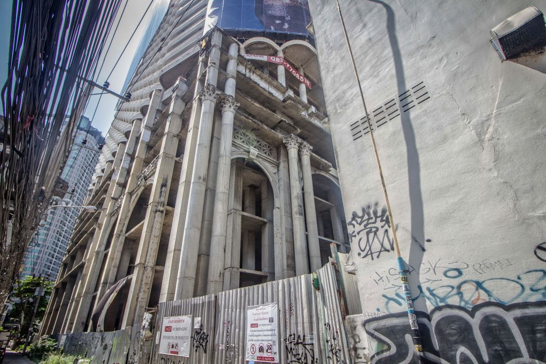 Unfinished concrete skyscraper overlooking graffiti-covered fence.