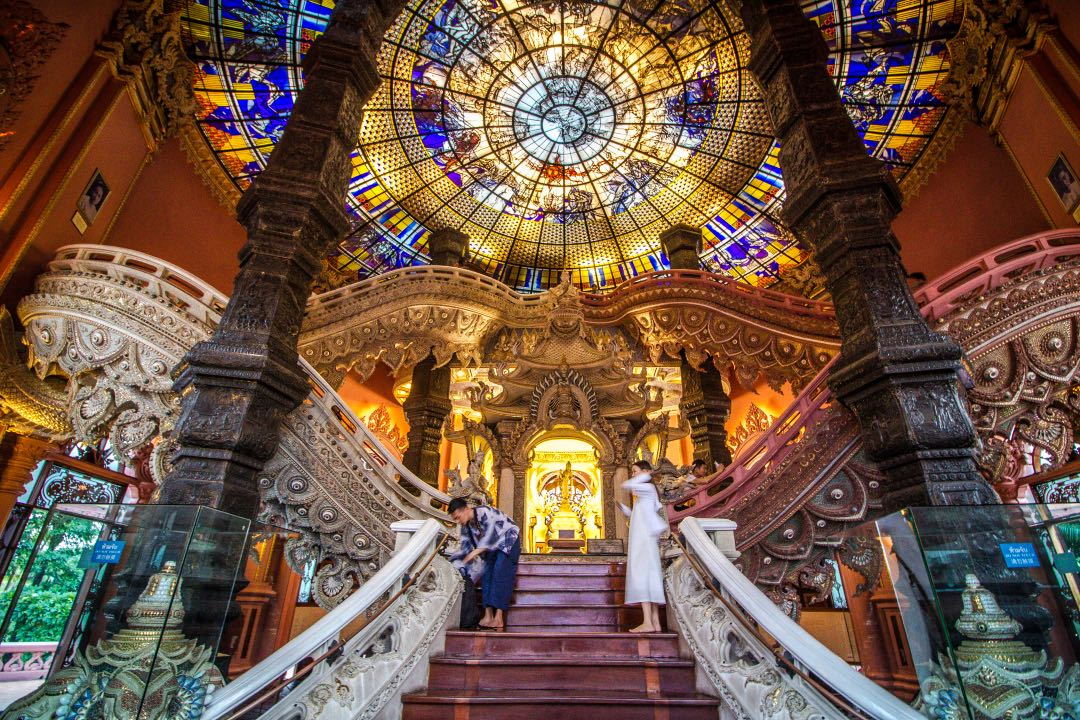 Couple taking photos on ornately carved staircase below a stained glass skylight.