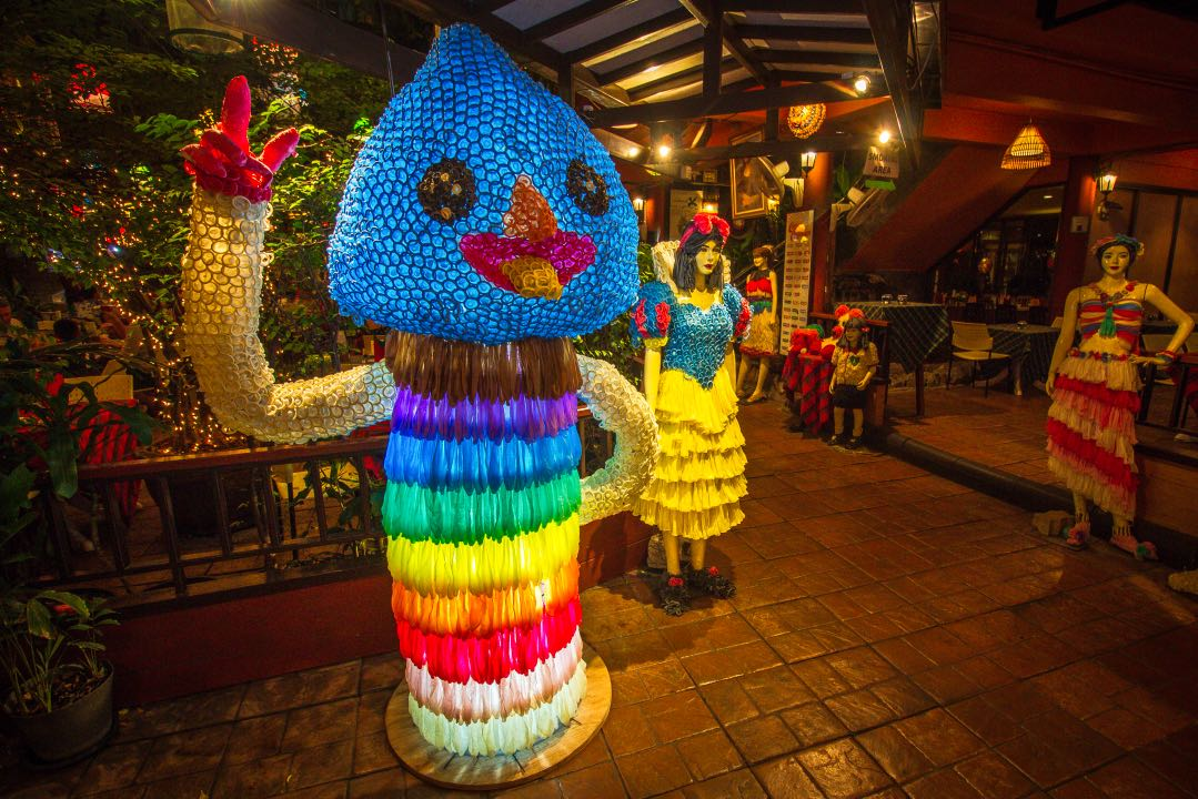 Human-sized phallic statue covered in neon-colored condoms. Mannequins in the background are wearing clothes made of condoms.