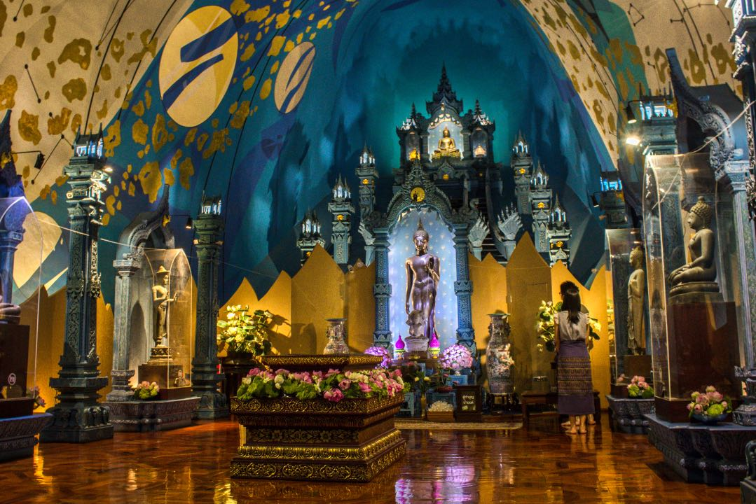 Buddhist shrine with blue and gold walls. Artwork on the ceiling depicting celestial bodies.