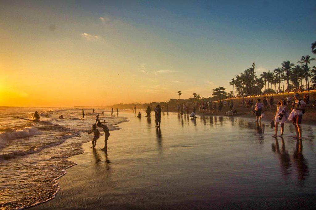 Dozens of tourists wandering around a sandy beach at sunset.