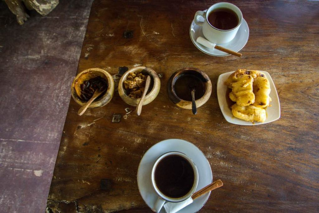 Two cups of coffee sits on saucers on a wooden table. Wooden bowls filled with sugar and spices sit next to a plate of cut up bananas.