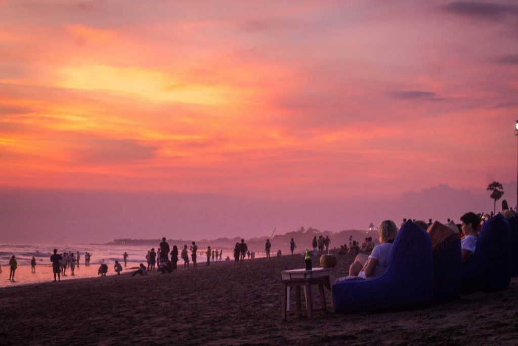 Crowd of people sitting in bean bag chairs on a beach watching a vibrant red sunset.