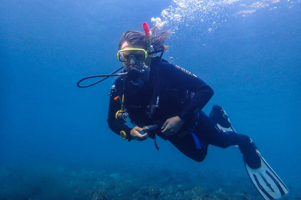 Man in scuba diving gear looking towards the camera against a murky ocean background.