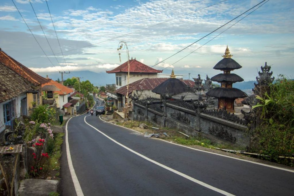 Narrow road running through a densely packed town with an ornate stone temple in the foreground.