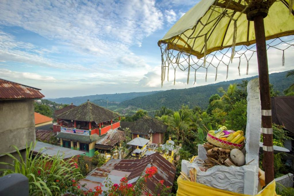 Colorful Balinese cityscape with a mountain forest in the background.