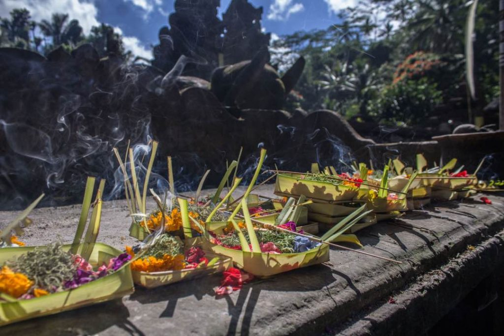 Woven coconut leaf baskets filled with lit incenses and flowers sits on stone altar.
