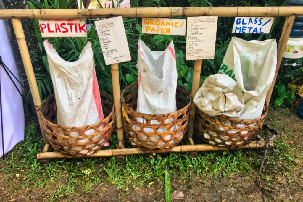 """Bamboo rack with three bags labeled """"Plastic,"""" """"Organic/Paper,"""" and """"Glass/Metal"""""""