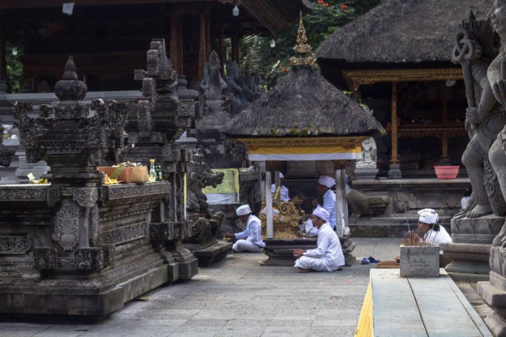 Men in white traditional clothing pray before a stone altar.