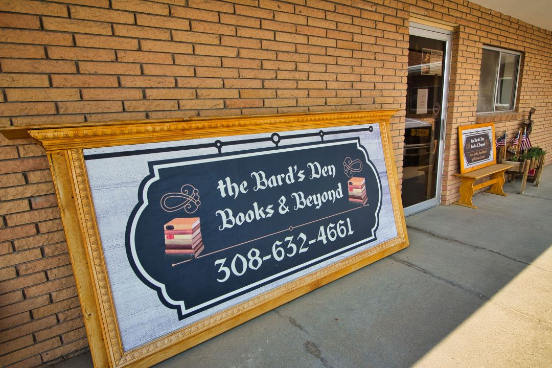 """Brick wall with a sign saying """"Bard's Den Books and Beyond"""" along with a phone number."""