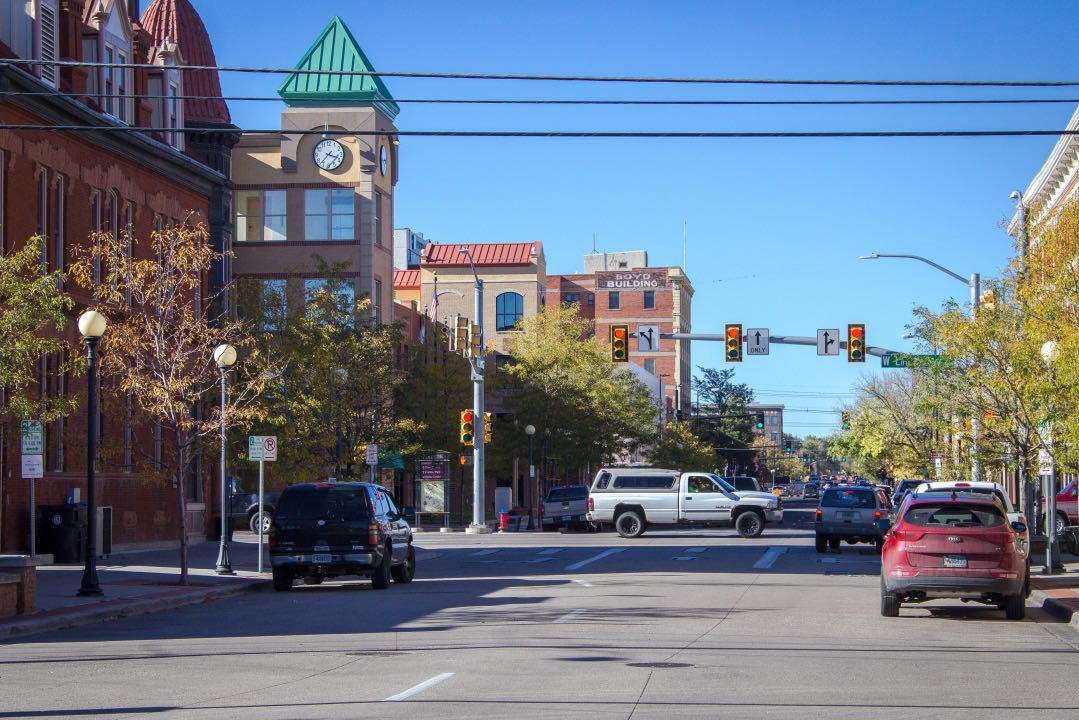 Intersection in the downtown area of a city with traffic signal and cars passing through.