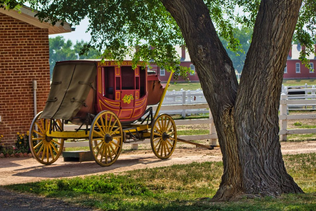 Red stagecoach with bright yellow wheels sitting in front of a red brick building and white corral fence.