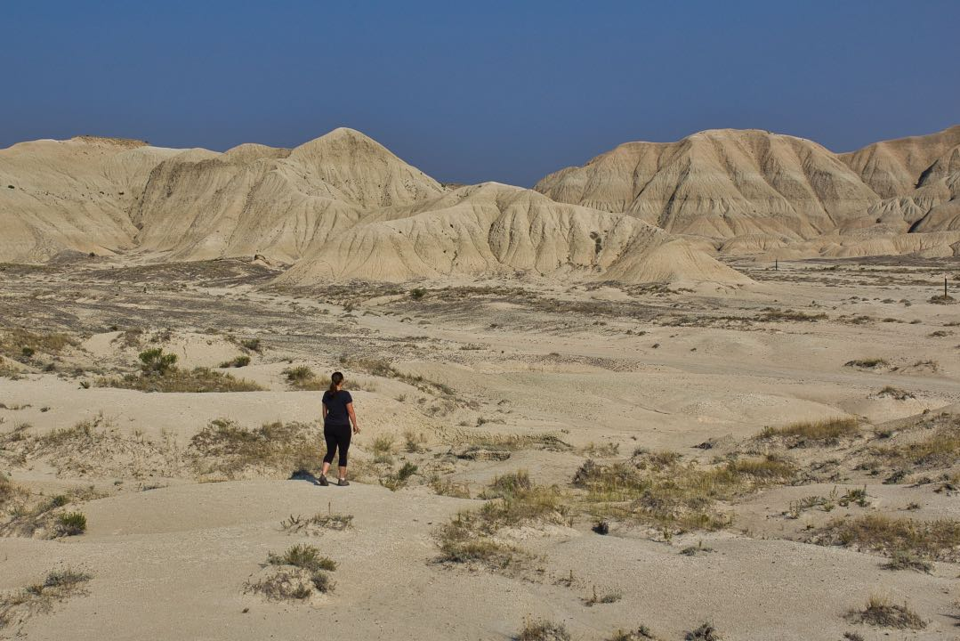Woman in black clothing walking through sand dunes with large badlands rock formations in the background.