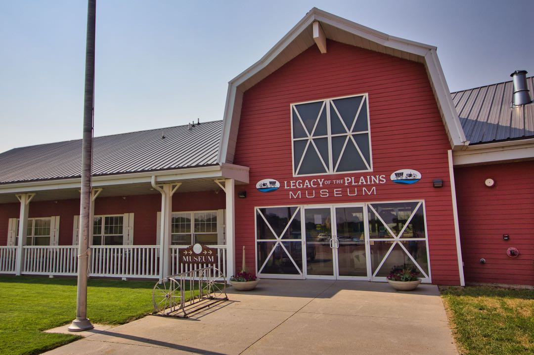 """Red barn-style building with signs saying """"Legacy of the Plains Museum""""."""