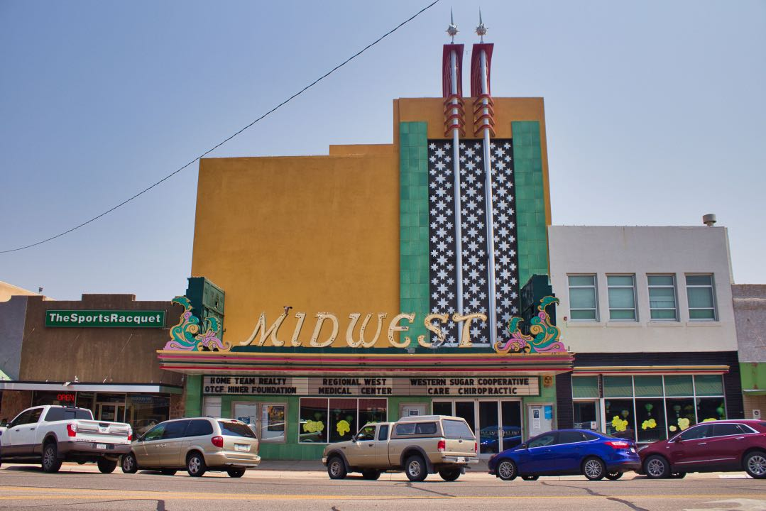"""Art Deco theater with retro marquee stating """"Midwest"""" with a line of cars angled parked in front of the building."""