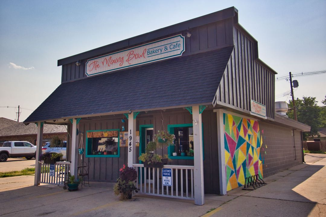 """Small cafe with awning and a sign saying """"The Mixing Bowl"""" above it and a mural of colorful triangles on the right side of it."""