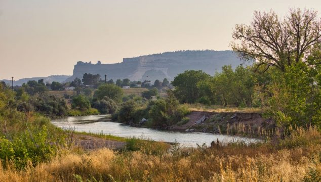 Slow moving river framed by prarie grasses and a very large mesa in the background.