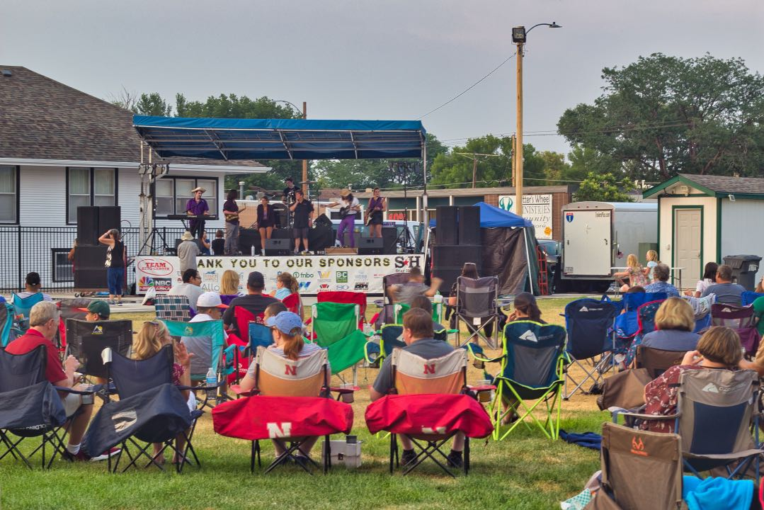 Rows of adults in folding chairs with a stage and five-person band playing music in the background.
