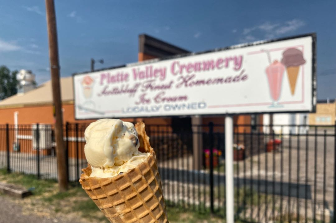 """Waffle cone with scoop of vanilla ice cream and a blurred sign saying """"Platte Valley Creamery"""" in the background."""