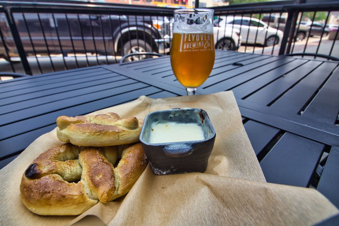 A black metal table with a piece of butcher paper holding a soft pretzel and cheese deep and a goblet of copper-hued beer in the background.