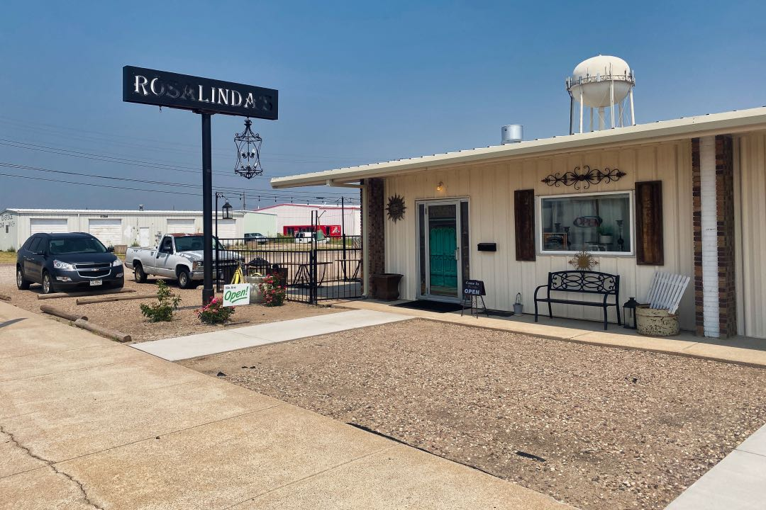 """Metal-sided building with water tower in the background and a partially painted over sign saying """"Rosalindas""""."""