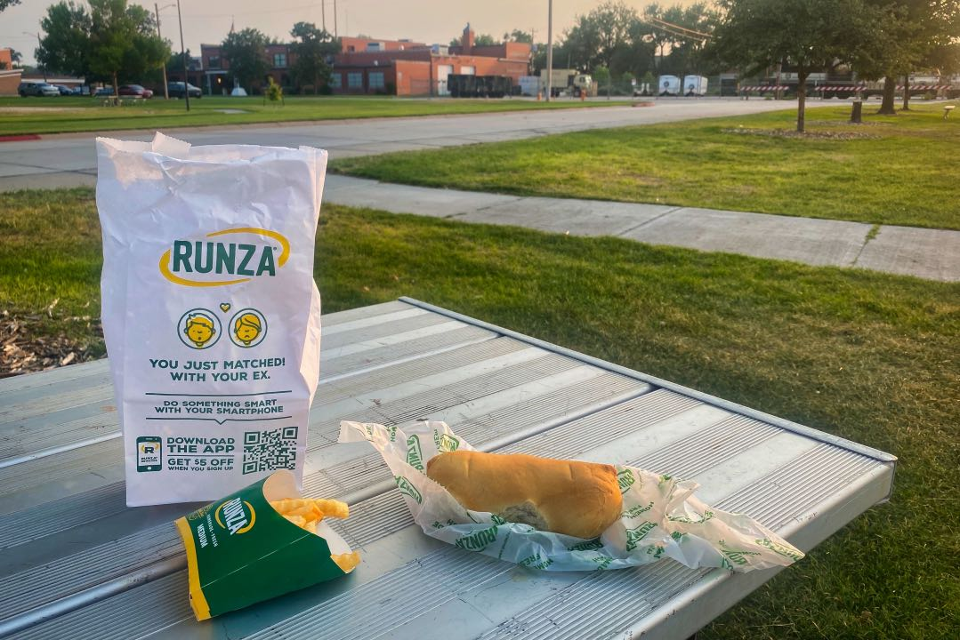 Picnic table with a Runza fast food bag, a box of crinkle-cut french fries, and a paper wrapping holding a bread pocket sandwich.