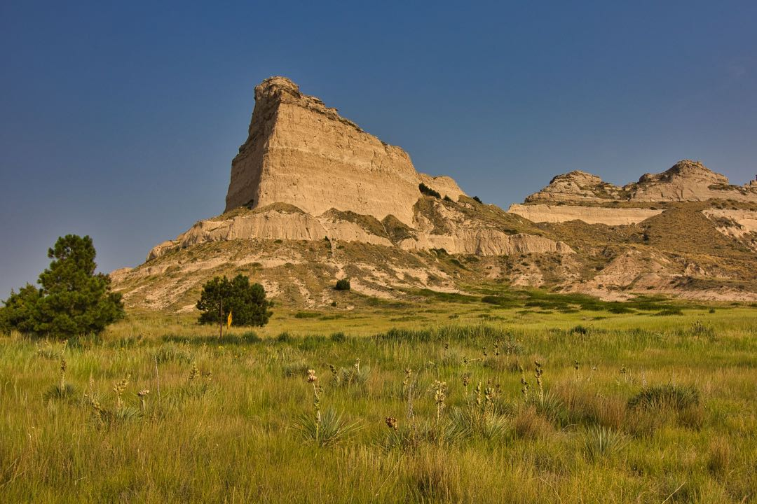 Angular rock formations abruptly rising from short grass prarie and a few trees in the foreground.