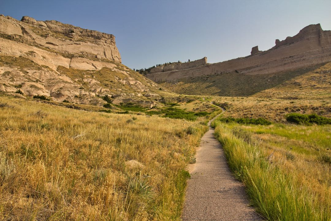Asphalt pathway leading through grassy prarie to a large sandstone rock formation in the background.