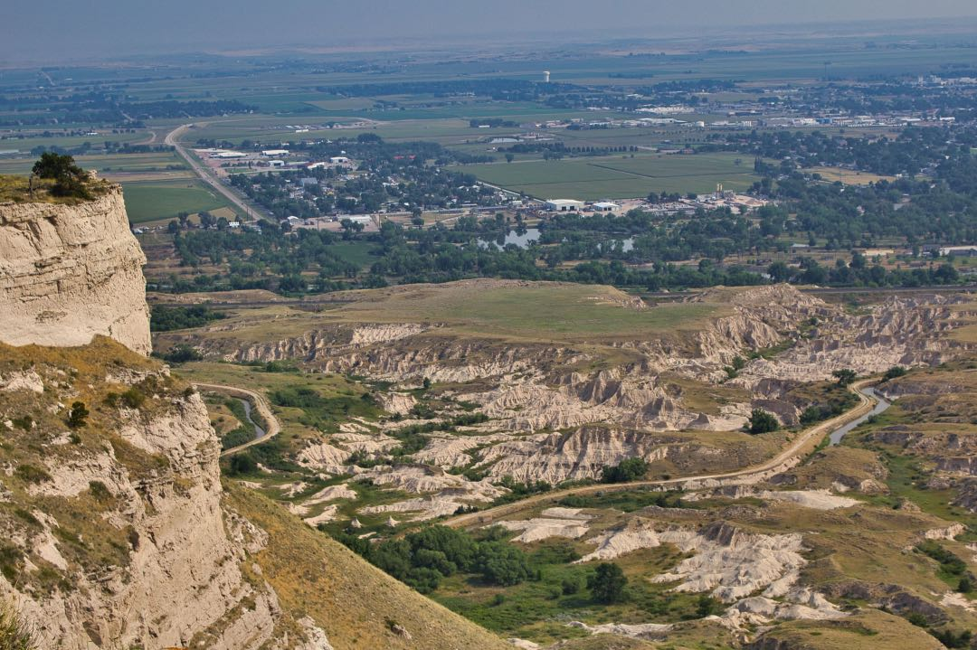 View from atop a tall rock formation with badlands and small cityscape in the background.