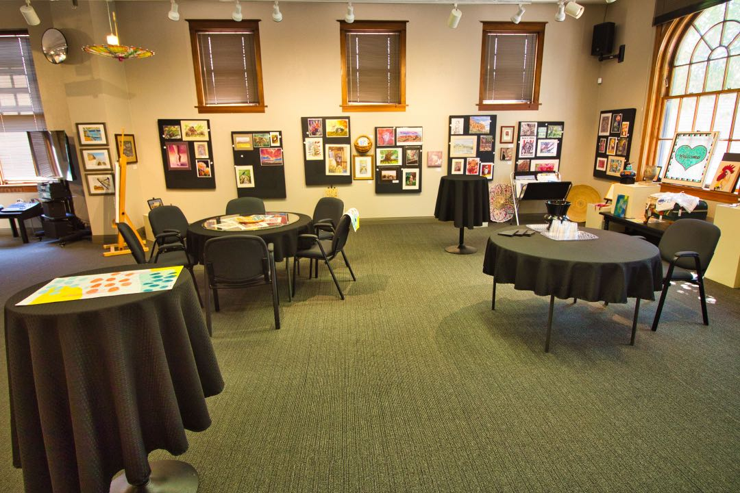 Three tables covered in black table clothes and numerous painting and artwork hung on the wall behind them.