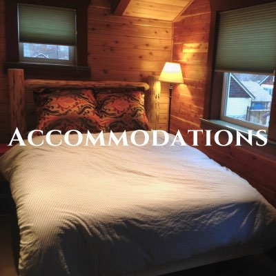 """""""Accommodations"""" written across a photo of a bed with a white duvet and wooden bed frame, inside a log cabin."""