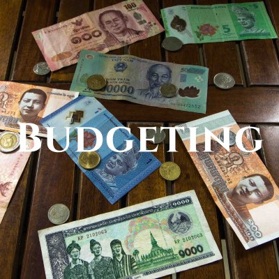 """""""Budgeting"""" written across a photo of coloring Thai baht and coins spread out on a wooden table."""
