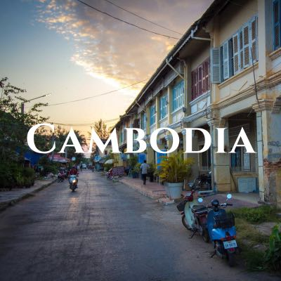 """""""Cambodia"""" written across a photo of motorbikes in a narrow street, lined on one side with yellow buildings with colorful shutters."""