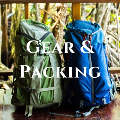 """""""Gear & Packing"""" written across a photo of two large backpacks sitting next to each other, one green and one blue."""