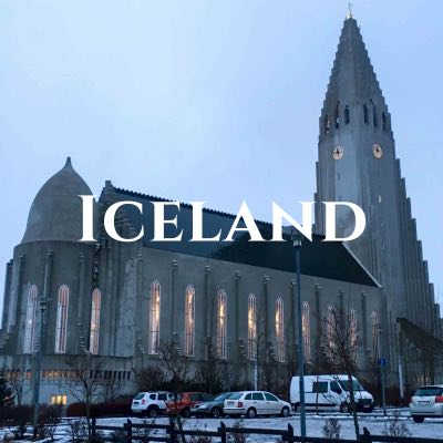 """""""Iceland"""" written across a photo of a church with a steeple and clock tower, with cars in the parking lot in front."""