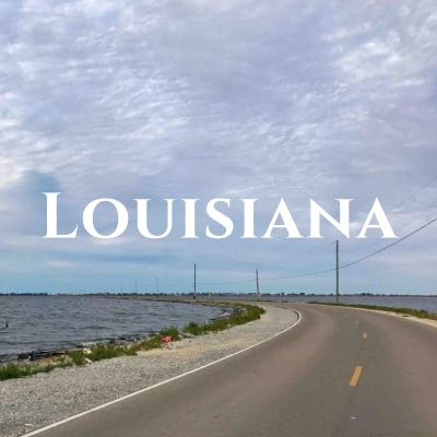 """""""Louisiana"""" written across a photo of a two-lane road stretching through water of the same height."""