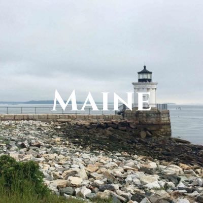 """""""Maine"""" written across a photo of a lighthouse facing the water."""